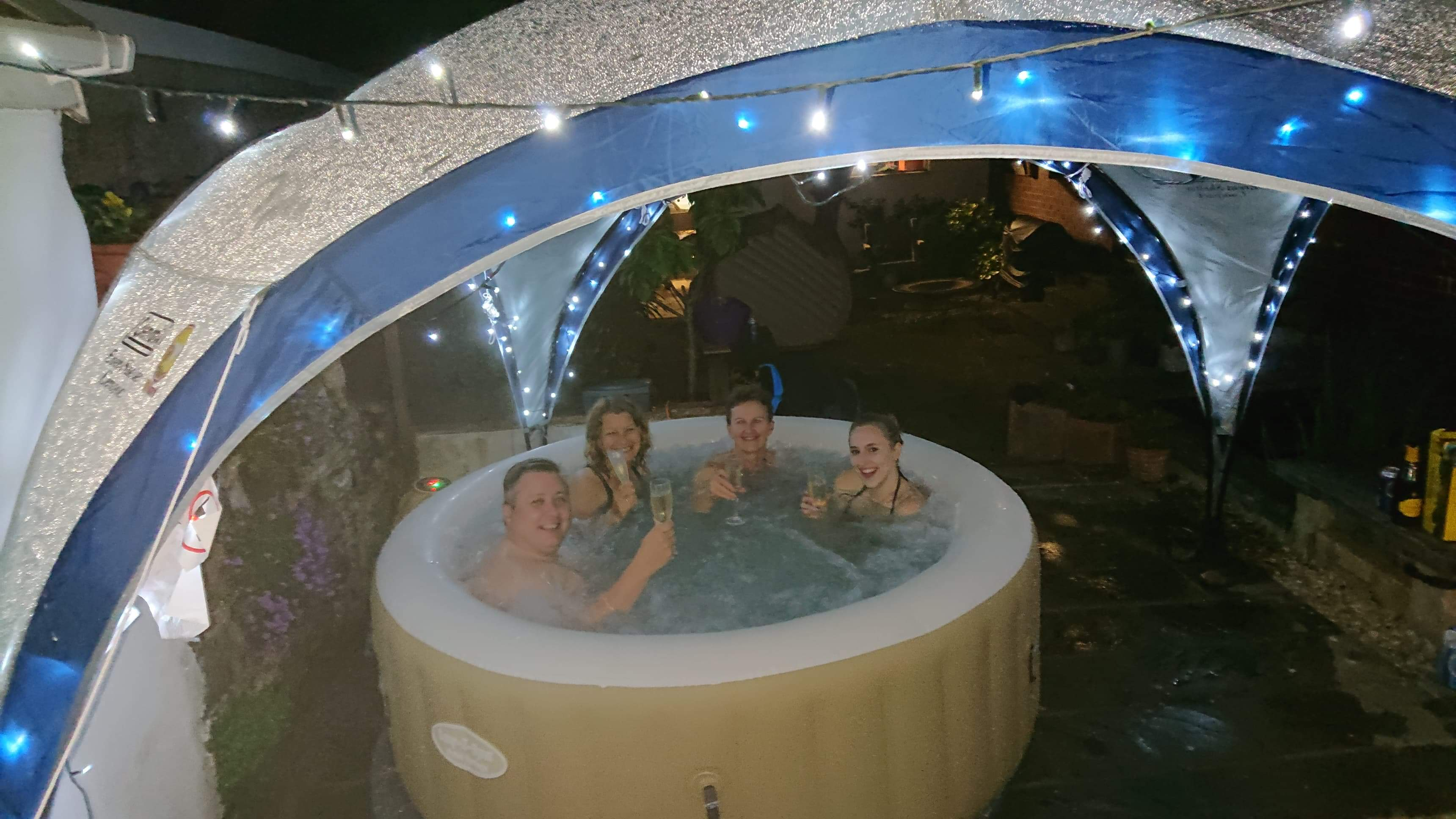 People drinking champagne in the hot tub at the Care For Kids North Devon Bubbles Party